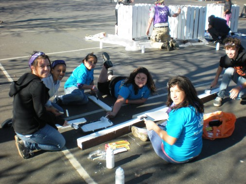 Young volunteers paint wood that will be used for a compost bin.