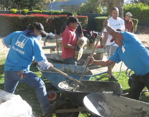 Volunteers mix cement to secure the playground structures.