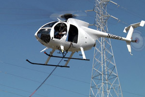 PG&E uses helicopters to transport crews and equipment to transmission towers near the San Mateo Bridge. (Currents Archive Photo.)