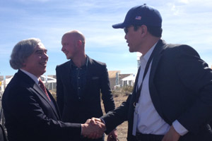 Energy Secretary Ernest Moniz greets Fong Wan, a PG&E senior vice president, at the Ivanpah event. (Photo by Lynsey Paulo.)